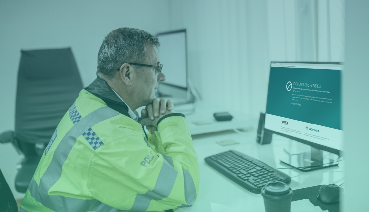 Police officer in hi vis jacket looking at a computer screen with the words 'Domain Suspended'